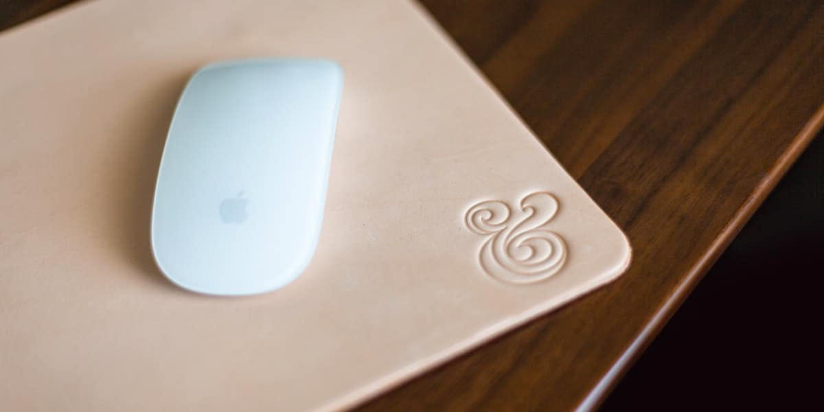 A computer mouse sitting on a mouse pad, on top of a wood desk.